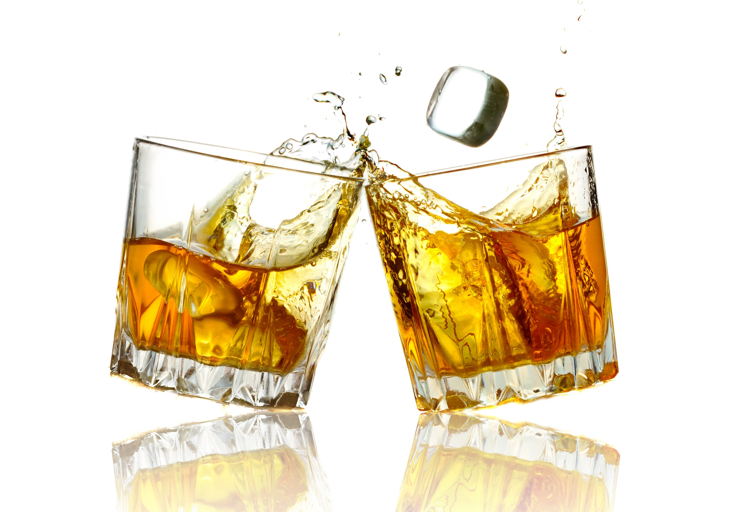 Two whiskey glasses clinking together, isolated 2